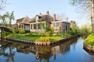 Beautiful traditional house with a thatched roof on a small island in a Dutch town of Giethoorn